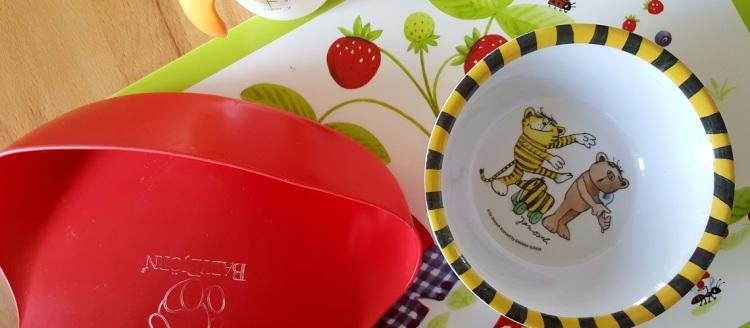 Lätzchen, Essschale, Trinkfläschen und Set auf dem Esstisch