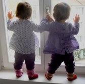 Zwillinge am Fenster stehend