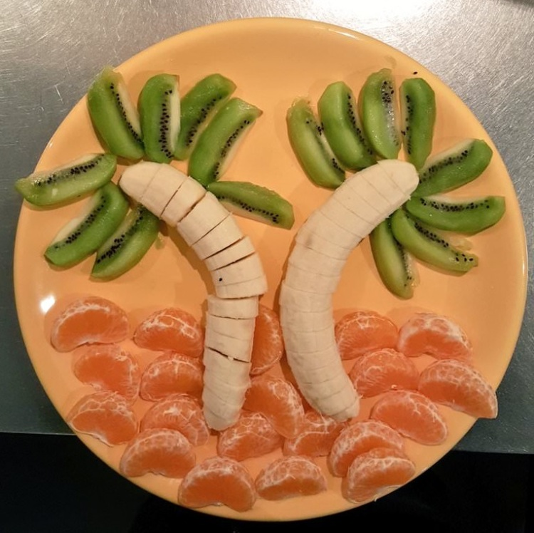 Teller mit Bananen, Mandarinenschnitzen und Kiwischnitzen in Form zweier Palmen und eines Sandstrands