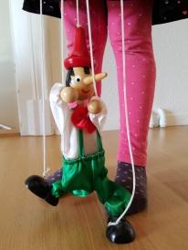 Eine der Zwillinge spielt mit einer Marionette