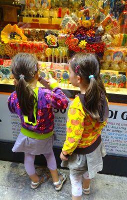 Die Zwillinge schauhen ins Schaufenster eines Süssigkeitenladens