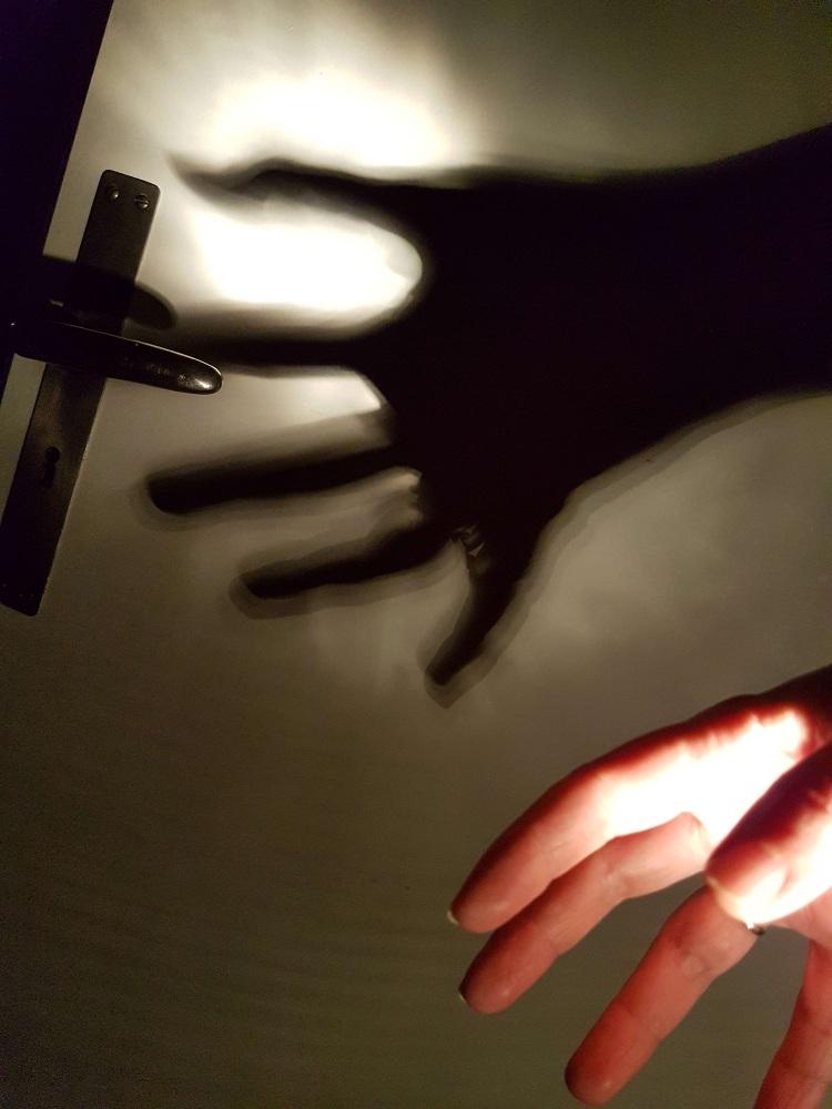 Eine beleuchtete Hand wirft einen gruseligen Schatten