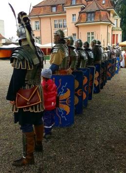 Eine der Zwillinge reiht sich bei exzerzierenden römischen Legionären ein